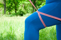 Een vette vrouw in een blauw kostuum op groen gras meet het volume van de heup met een metende band stock foto's