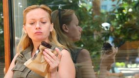 Een vette vrouw eet een cupcake in een koffie en slokjes onderaan koffie, 4k, langzame motie stock footage
