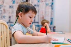 Een vier éénjarigenkind trekt met kleurpotloden Stock Fotografie