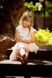 Een vier éénjarigenmeisje zit op een houten trap stock afbeelding