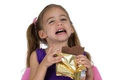 Een vier-jaar-oud meisje lijdt aan een tandpijn terwijl het eten van chocolade Stock Foto