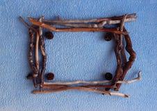Een vierkant kader van larikskegels en droge stokken op een blauwe backgroun Stock Afbeeldingen