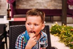 Een vijf-jaar-oud kind eet chocoladeroomijs in een wafelkegel in de zomer royalty-vrije stock afbeeldingen