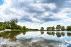 Een vijver met een bewolkte hemel Royalty-vrije Stock Foto's