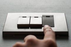 Een vinger zet een lichte schakelaar aan royalty-vrije stock afbeelding