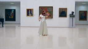 Een violist presteert in een alleen museumruimte die, zich in een centrum bevinden stock video