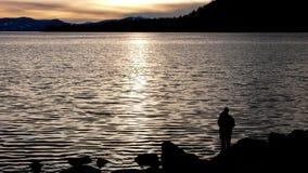 Een visser bij zonsondergang bij Meer Tahoe, Nevada in Hellingsdorp stock foto