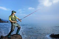 Een visser die bij het overzees vist stock foto's