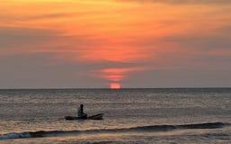 Een visser die bij zonsondergang paddelen stock afbeeldingen
