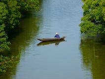 Een visser die op een rivier roeien royalty-vrije stock fotografie