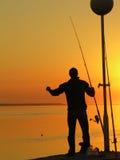 Een visser die zich door de zonsondergang bevindt Royalty-vrije Stock Foto