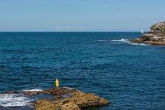 Een visser in een geel regenjasje die langs Bondi aan de kustgang van Coogee, Sydney, Australië vissen Stock Fotografie