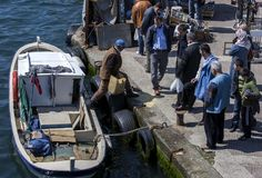 Een visser maakt zijn die vangst van een boot leeg op Gouden Hoorn in Istanboel in Turkije wordt gedokt Royalty-vrije Stock Foto