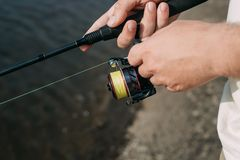 Een visser met een hengel op de rivierbank stock foto's