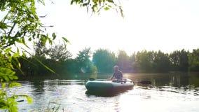 Een visser op een boot vaart op de meer het roeien roeispanen stock videobeelden