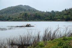 Een visser werkt in zijn botenhuis over Samorthong-reservoir Royalty-vrije Stock Foto