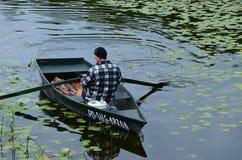 Een visser in zijn boot bij meer in Polen stock fotografie