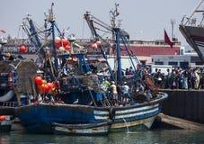 Een visserijtreiler komt in dok dat door een grote menigte bij de bezige vissershaven van Essaouira in Marokko aan moet worden be Royalty-vrije Stock Afbeelding