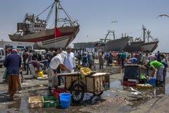 Een visserijtreiler zit in droogdok aangezien vissenmonger vissen in Essaouira in Marokko verkoopt Royalty-vrije Stock Afbeelding