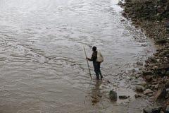 Een vissers dragende zak met een bamboepool, zal aan de getijdevlakte Stock Fotografie