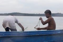 Een vissersmens bevindt zich op zijn boot met een stapel van visnet stock fotografie