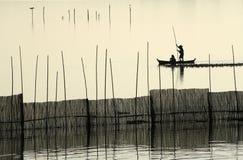 Een visserssilhouet dichtbij de Brug van U Bein. Stock Foto