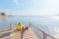 Een visserszitting ter plaatse dichtbij het overzees met zon lichte middag stock afbeelding