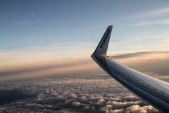Een vleugel van een Ryanair-vliegtuig die bij zonsondergang landen stock foto's
