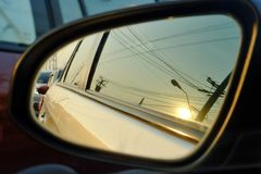 Een vleugelspiegel van een auto met van het zon de lichte bezinning en onduidelijke beeld achtergrond van het straatgebied stock foto