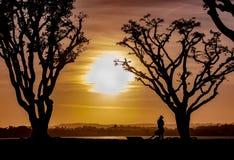 Een Vliegervlieger verpakt omhoog Zijn Vliegers bij Zonsondergang stock foto's
