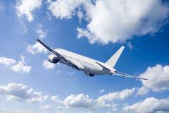 Een vliegtuig dat in de blauwe hemel vliegt Stock Foto's