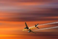 Een vliegtuig die in een mooie zonsondergang vliegen Stock Afbeeldingen