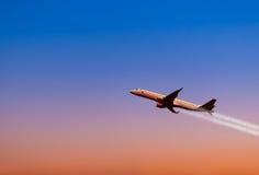 Een vliegtuig die in een mooie zonsondergang vliegen Stock Foto's