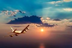 Een vliegtuig die in een mooie zonsondergang vliegen Royalty-vrije Stock Foto's