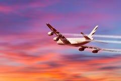 Een vliegtuig die in een mooie zonsondergang vliegen Stock Afbeelding