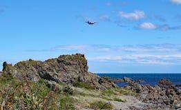 Een vliegtuig maakt het is definitieve benadering van Wellington Airport over de ruwe kust van de Kok Straits stock fotografie