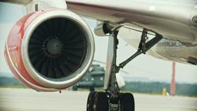 Een vliegtuig op het luchthavengebied - warme lucht die uit de turbine komt stock videobeelden