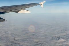 Een vliegtuig zilveren vleugel tijdens een vlucht over witte wolken en een optisch fenomeen van de cirkelhalo op de foto royalty-vrije stock foto
