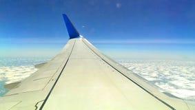 Een vliegtuigvleugel van een straalvoering hoog over het landschap Stock Afbeelding