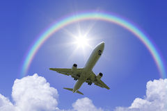 Een vliegtuigvlieg over de regenboog Stock Afbeeldingen