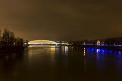 Een Vltava-rivier in Praag met een nieuwe glanzende brug die het kruisen bij nacht Stock Afbeelding