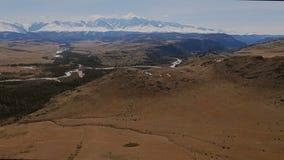 Een vlucht over een mooie vallei met sneeuwbergen in de afstand stock video
