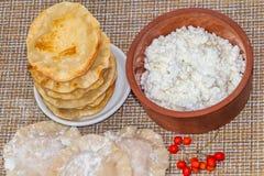 Een voedselvlakte legt van de gebraden gele tortilla's met kwark ligt als een piramide op een kleine witte plaat en een klei royalty-vrije stock fotografie