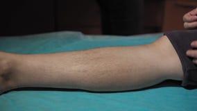 Een voet met lange zwarte haren op een blauw beschikbaar bedblad stock video