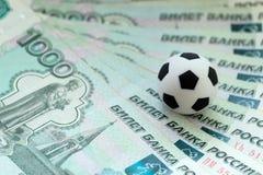 Een voetbalbal op Russische bankbiljetten met een nominale waarde van duizend roebels Close-up Het concept corruptie, steekpennin stock fotografie
