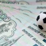 Een voetbalbal op Russische bankbiljetten met een nominale waarde van duizend roebels Close-up Vierkant frame Het concept corrupt stock afbeelding