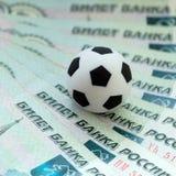 Een voetbalbal op Russische bankbiljetten met een nominale waarde van duizend roebels Het concept corruptie, steekpenningen of sp royalty-vrije stock foto