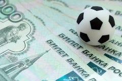 Een voetbalbal op Russische bankbiljetten van duizend roebels Het concept corruptie, steekpenningen of sporten het wedden Sluit o royalty-vrije stock foto's