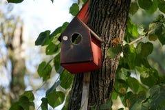 Een vogelhuis van triplex, geschilderde rode boom die met groot wordt gemaakt stock foto's