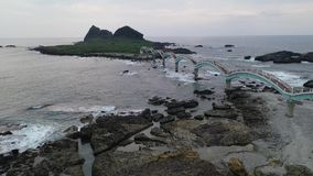 Een vogelperspectief over een mooi zeedieeiland door een acht-boog brug met rotsachtig wordt verbonden stock videobeelden